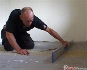 Проверка плоскости пола при помощи уровня